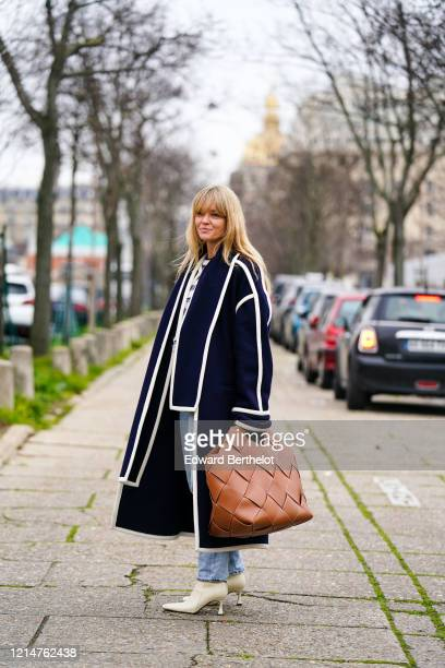 Jeanette Madsen wears a dark blue long coat a brown leather woven large bag blue denim jeans pants white pointy shoes outside Loewe during Paris...