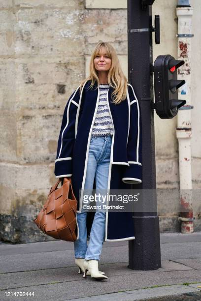 Jeanette Madsen wears a dark blue long coat, a brown leather woven large bag, blue denim jeans pants, white pointy shoes, outside Loewe, during Paris...
