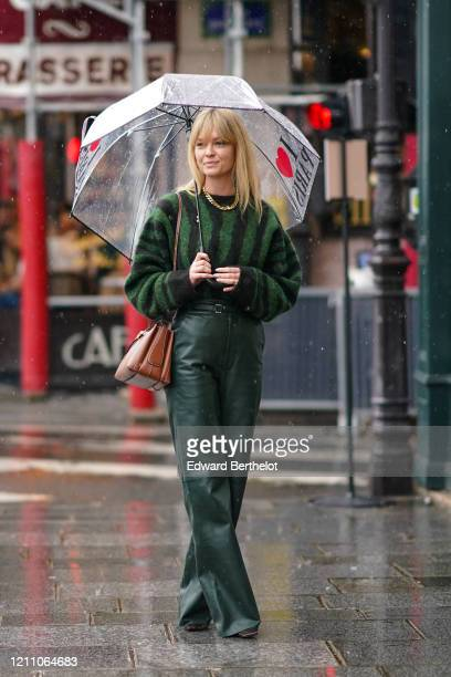 Jeanette Madsen wears a green and black striped wool pullover green flared leather pants a brown leather bag a golden necklace during Paris Fashion...