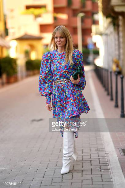 Jeanette Madsen wears a multicolor floral print dress a green bag a belt white high boots outside Marni during Milan Fashion Week Fall/Winter...