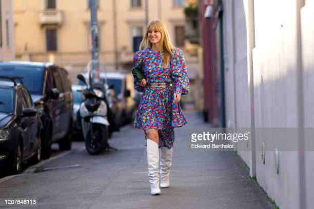 Jeanette Madsen wears a multicolor floral print dress, a green bag, a belt, white high boots, outside Marni, during Milan Fashion Week Fall/Winter...