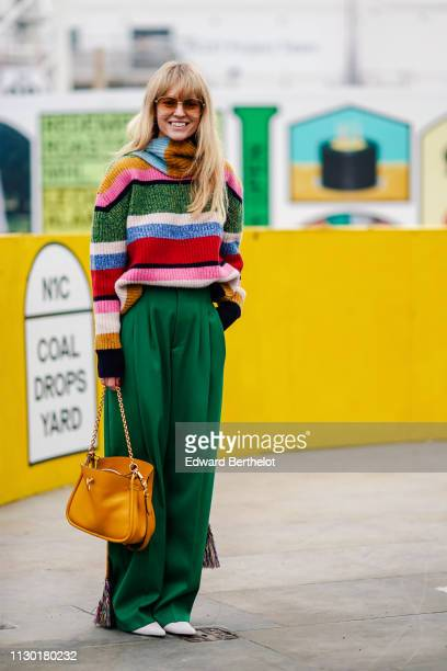 Jeanette Madsen wears a multicolor striped wool pullover a long scarf green flare fluid pants white shoes an orange bag during London Fashion Week...