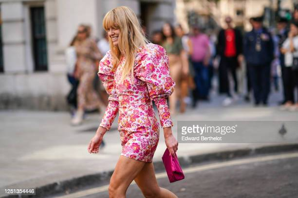 Jeanette Madsen wears a pink ruffled short floral print dress with puff shoulders, a pink/purple bag, during London Fashion Week September 2019 on...