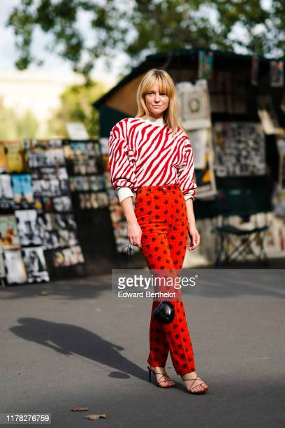 Jeanette Madsen wears a red and white striped zebra pattern print pullover with shoulder pads red pants with printed features a black bag shaped as a...