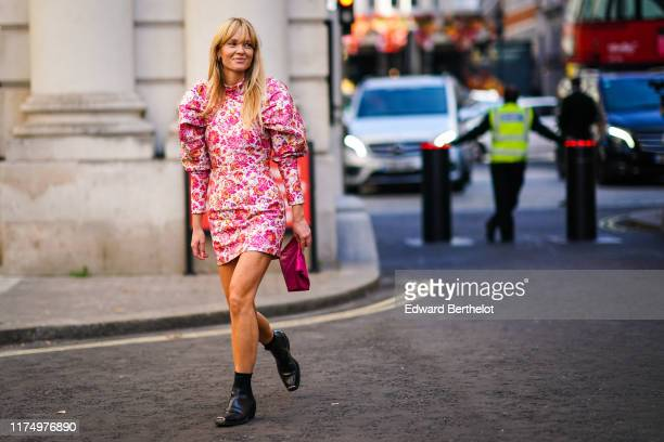Jeanette Madsen wears a ruffled puff shoulder pink floral print dress a pink clutch black leather shoes during London Fashion Week September 2019 on...