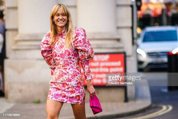 Jeanette Madsen wears a ruffled puff shoulder pink floral print dress a pink clutch during London Fashion Week September 2019 on September 15 2019 in...