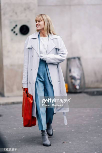 Jeanette Madsen wears a trench coat blue pants a red bag a white top gray shoes outside Cedric Charlier during Paris Fashion Week Womenswear...