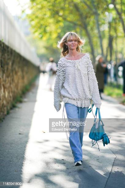 Jeanette Madsen wears a white bejewelled top with attached pearls a blue Loewe bag white pointy shoes blue flared denim pants outside Loewe during...