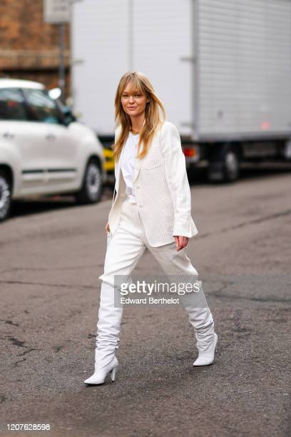 Jeanette Madsen wears a white blazer jacket a white tshirt white pants pointy boots a quilted bag outside Max Mara during Milan Fashion Week...