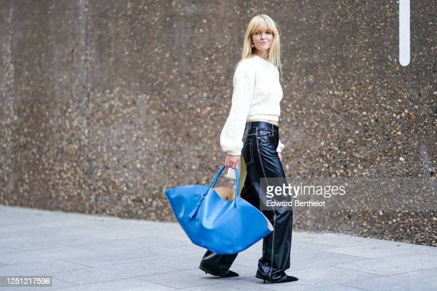 Jeanette Madsen wears a white knitted wool pullover a blue leather large bag black leather pants pointy shoes during London Fashion Week September...