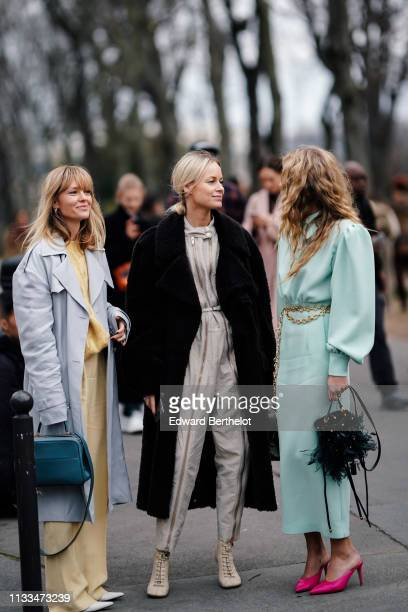Jeanette Madsen wears a yellow pantsuit a blue bag a grey trench coat white pointy shoes Thora Valdimars wears a grey jumpsuit a black fluffy coat...
