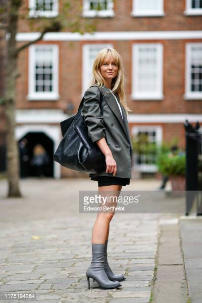 Jeanette Madsen wears an oversized blazer jacket with rolledup sleeves a black leather large Celine bag gray leather high heels boots during London...