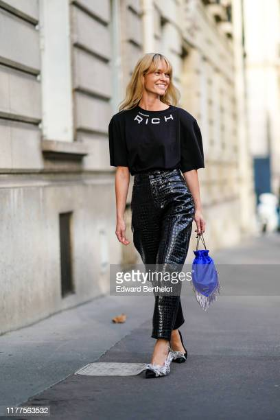 Jeanette Madsen wears earrings, a black Alessandra Rich t-shirt, shiny black crocodile pattern high waist leather pants, a blue fringy bag, black...