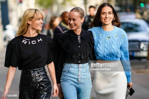 Jeanette Madsen wears earrings, a black Alessandra Rich t-shirt, shiny black crocodile pattern high waist leather pants ; Thora Valdimars wears a...