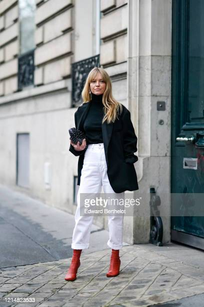 Jeanette Madsen wears earrings a black turtleneck pullover a black oversized blazer jacket white pants red leather boots a black bag with polka dots...
