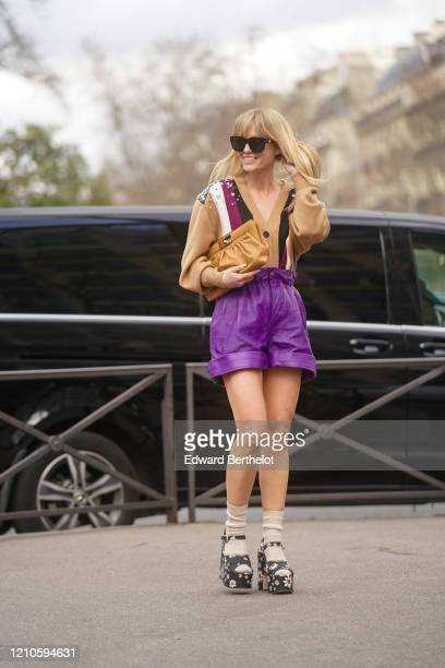 Jeanette Madsen wears sunglasses, a brown leather puff bag, a v-neck wool bejeweled vest, purple leather shorts, wool socks, floral print shoes,...