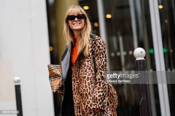 Jeanette Madsen wears sunglasses a leopard print coat an orange top black pants white shoes during Paris Fashion Week Womenswear Fall/Winter...