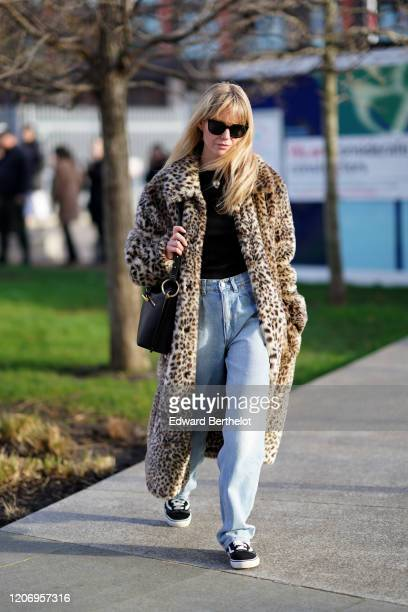 Jeanette Madsen wears sunglasses a leopard print fluffy faux fur coat a black top blue denim jeans a black leather bag sneakers during London Fashion...