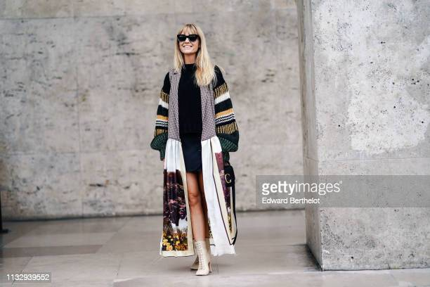 Jeanette Madsen wears sunglasses a multicolor long jacket with printed picture depicting nature a Chloe bag a black dress outside Atlein during Paris...