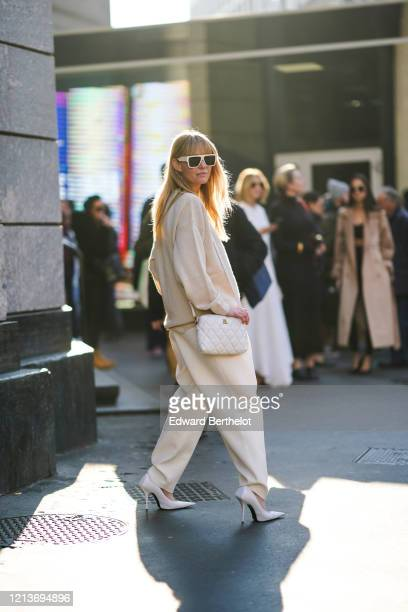 Jeanette Madsen wears sunglasses earrings a Balenciaga creamcolor sweater creamcolor widelegs pants a white quilted bag white pointy heeled pumps a...
