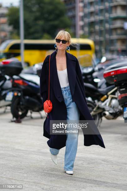 Jeanette Madsen wears sunglsses, blue earrings, a dark coat, a red bag, a white low neck top, blue flared denim jeans, white shoes, outside the...