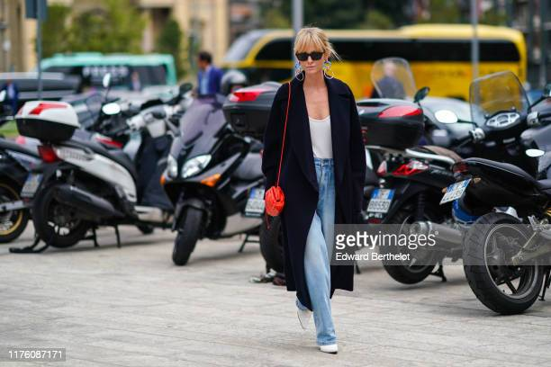 Jeanette Madsen wears sunglsses blue earrings a dark coat a red bag a white low neck top blue flared denim jeans white shoes outside the Sportmax...