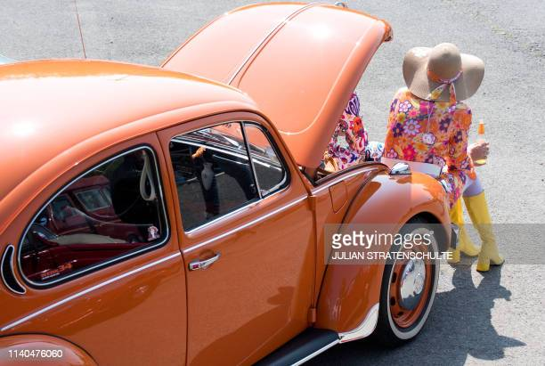 Jeanette Nietmann wears a hippy dress as she sits in front of her vintage Volkswagen beetle car at the 36th Maikaefertreffen in Hanover northern...