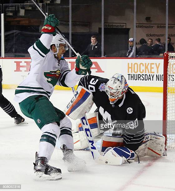 JeanFrancois Berube of the New York Islanders covers the puck during the first period against the Minnesota Wild at the Barclays Center on February 2...