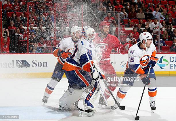 JeanFrancois Berube of the New York Islanders is snowed in the crease as teammates Cal Clutterbuck and Calvin deHaan help defend during an NHL game...