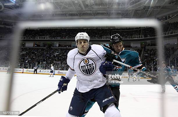 JeanFrancois Jacques of the Edmonton Oilers is hit by Ryane Clowe of the San Jose Sharks at HP Pavilion on December 21 2010 in San Jose California