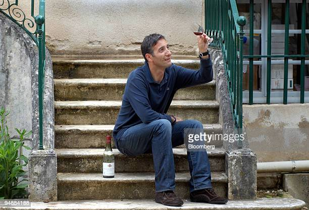 Jean-Francois Rateau, manager of the cellar at the Clos Saint Jean vineyard, checks a glass of the wine in the Burgundy village of...