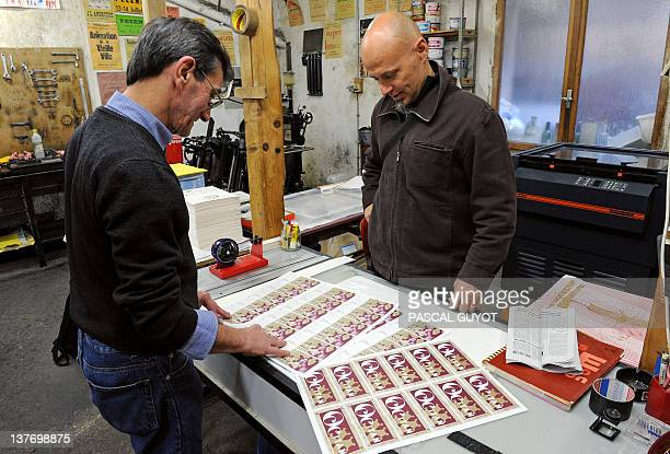 JeanFrançois Marques and printer JeanClaude Domens look at local Occitan currency notes showing a portrait of French playwright and actor Moliere on...