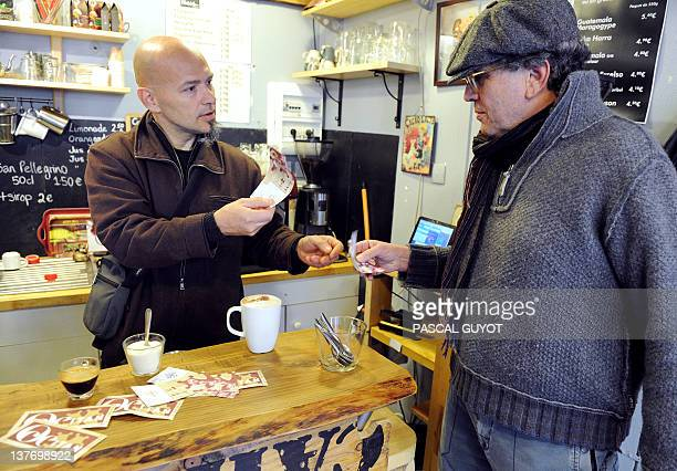 JeanFrançois Marques looks at a customer paying for a coffee with local Occitan currency notes showing a portrait of French playwright and actor...