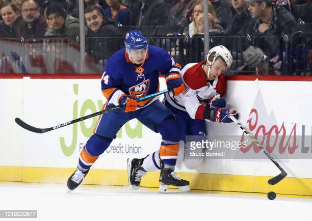 JeanGabriel Pageau of the New York Islanders checks Brett Kulak of the Montreal Canadiens into the boards during the first period at the Barclays...