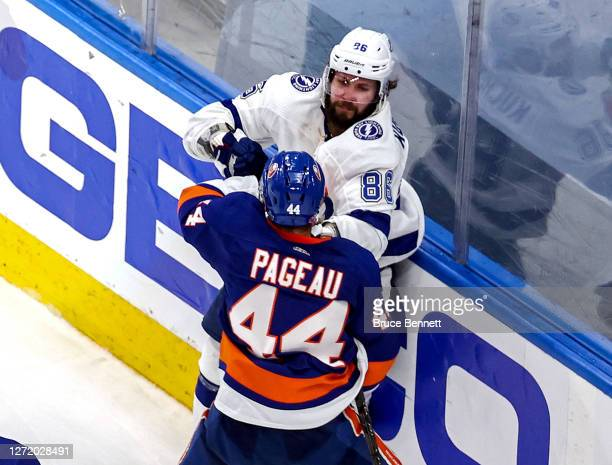 Jean-Gabriel Pageau of the New York Islanders fights with Nikita Kucherov of the Tampa Bay Lightning after scoring an empty-net goal while being...