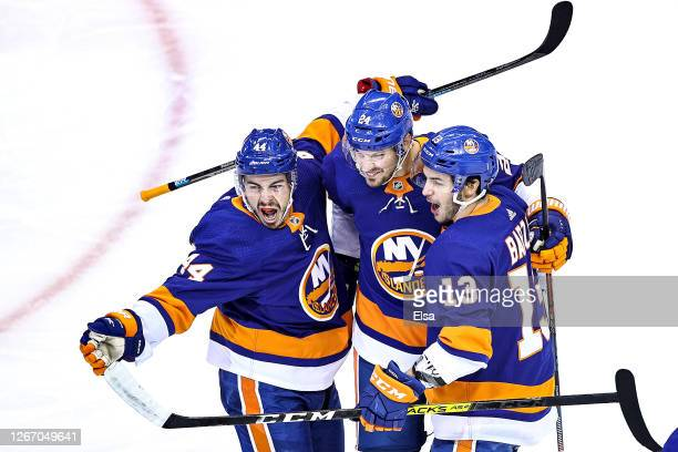 Jean-Gabriel Pageau of the New York Islanders is congratulated by his teammates, Scott Mayfield and Mathew Barzal after scoring a goal at 3:50...