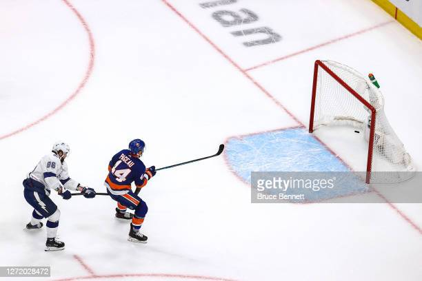 Jean-Gabriel Pageau of the New York Islanders scores an empty-net goal while being slashed by Nikita Kucherov of the Tampa Bay Lightning during the...