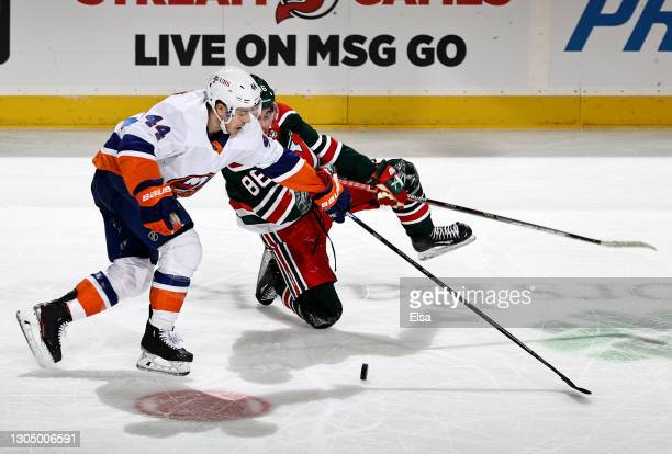 Jean-Gabriel Pageau of the New York Islanders shoves Jack Hughes of the New Jersey Devils in the third period at Prudential Center on March 02, 2021...