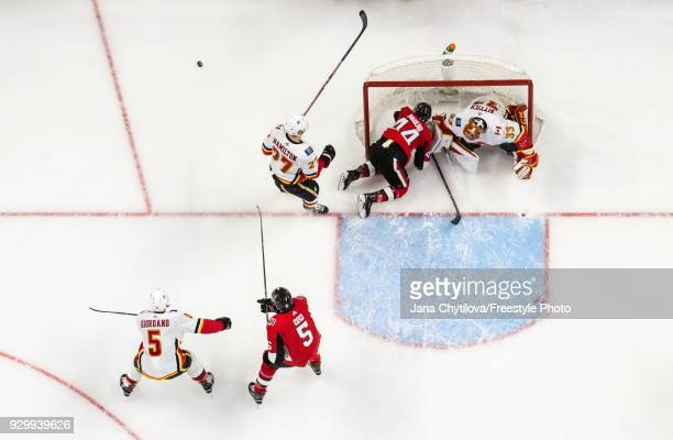 JeanGabriel Pageau of the Ottawa Senators end up on his knees in the net along with David Rittich of the Calgary Flames after Dougie Hamilton of the...