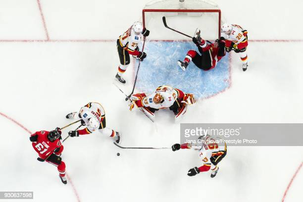 JeanGabriel Pageau of the Ottawa Senators falls to the ice as teammate Mark Stone battles for puck possession against Mark Giordano and Sam Bennett...