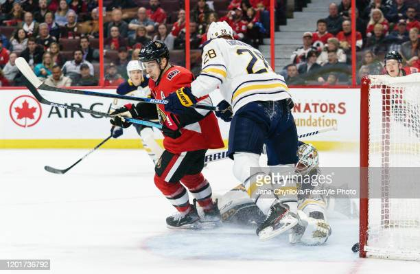 JeanGabriel Pageau of the Ottawa Senators gets the puck past the outstretched trapper of Carter Hutton of the Buffalo Sabres as Zemgus Girgensons of...