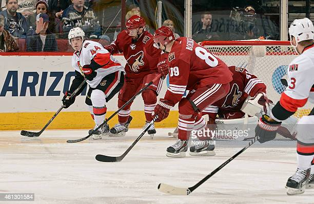 JeanGabriel Pageau of the Ottawa Senators looks to pass the puck around Sam Gagner and Mikkel Boedker of the Arizona Coyotes during the second period...