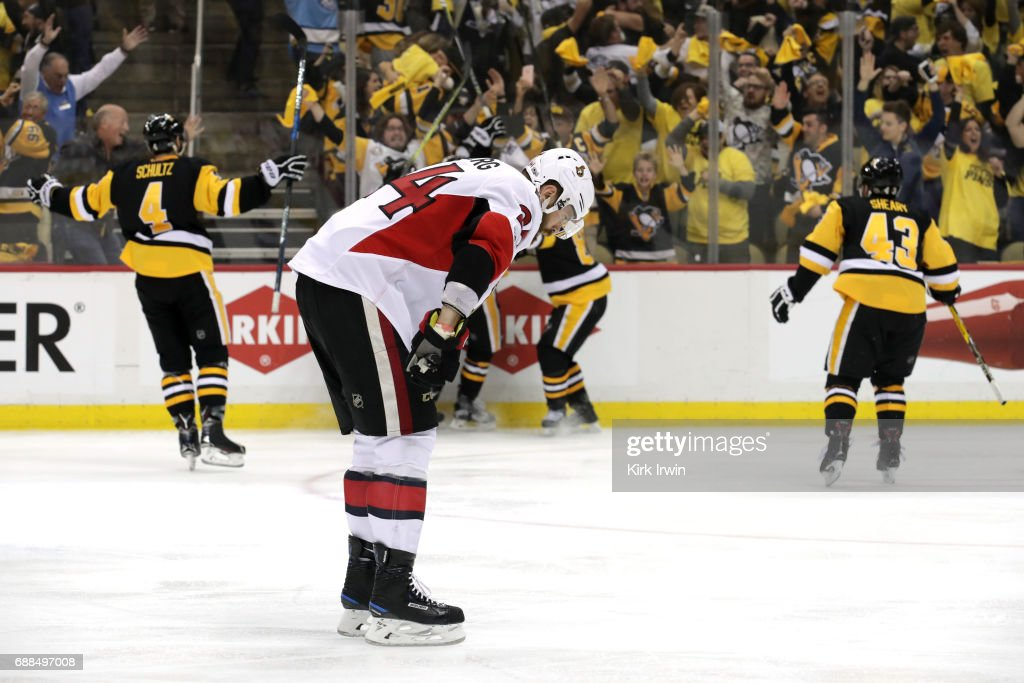 Jean-Gabriel Pageau #44 of the Ottawa Senators reacts as Chris Kunitz #14 of the Pittsburgh Penguins celebrates with Sidney Crosby #87, Ian Cole #28, Justin Schultz #4 and Conor Sheary #43 after scoring the game winning goal agianst Craig Anderson #41 of the Ottawa Senators in the second overtime with a score of 3 to 2 in Game Seven to win the Eastern Conference Final during the 2017 NHL Stanley Cup Playoffs at PPG PAINTS Arena on May 25, 2017 in Pittsburgh, Pennsylvania.