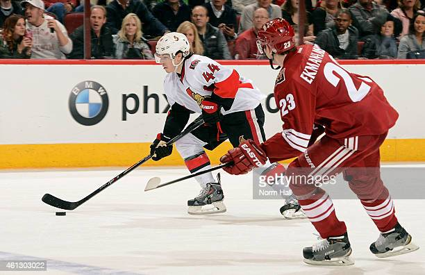 JeanGabriel Pageau of the Ottawa Senators skates with the puck ahead of Oliver EkmanLarsson of the Arizona Coyotes during the second period at Gila...