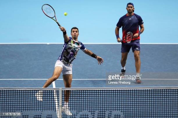 JeanJulien Rojer of The Netherlands playing partner of Horia Tecau of Romania plays a forehand volley in their doubles match against Nicolas Mahut...