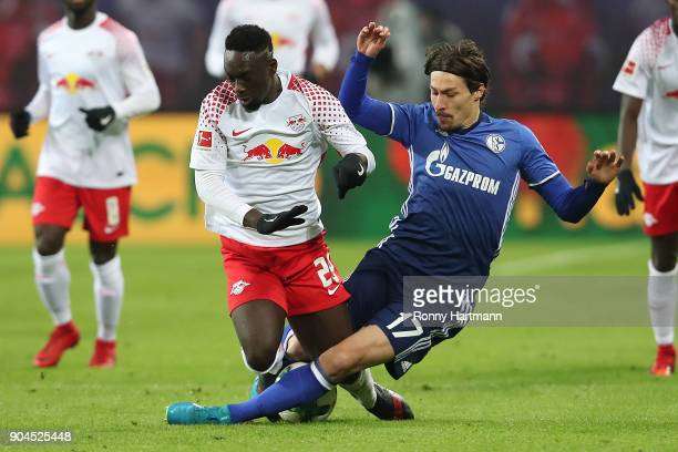 JeanKevin Augustin of Leipzig fights for the ball with Benjamin Stambouli of Schalke during the Bundesliga match between RB Leipzig and FC Schalke 04...
