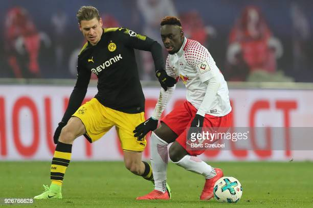 JeanKevin Augustin of Leipzig fights for the ball with Lukasz Piszczek of Dortmund during the Bundesliga match between RB Leipzig and Borussia...