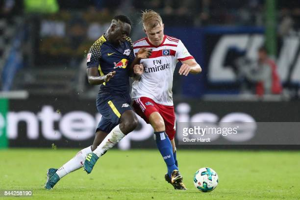 JeanKevin Augustin of Leipzig is challenged by Rick van Drongelen of Hamburg during the Bundesliga match between Hamburger SV and RB Leipzig at...