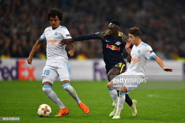 JeanKevin Augustin of RB Leipzig is challenged by Luiz Gustavo and Maxime Lopez of Olympique Marseille during the UEFA Europa League quarter final...