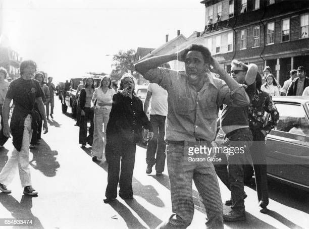JeanLouis Andre Yvon stands in the center of a street in South Boston surrounded by a group of white men and women on Oct 7 1974 Yvon was trying to...